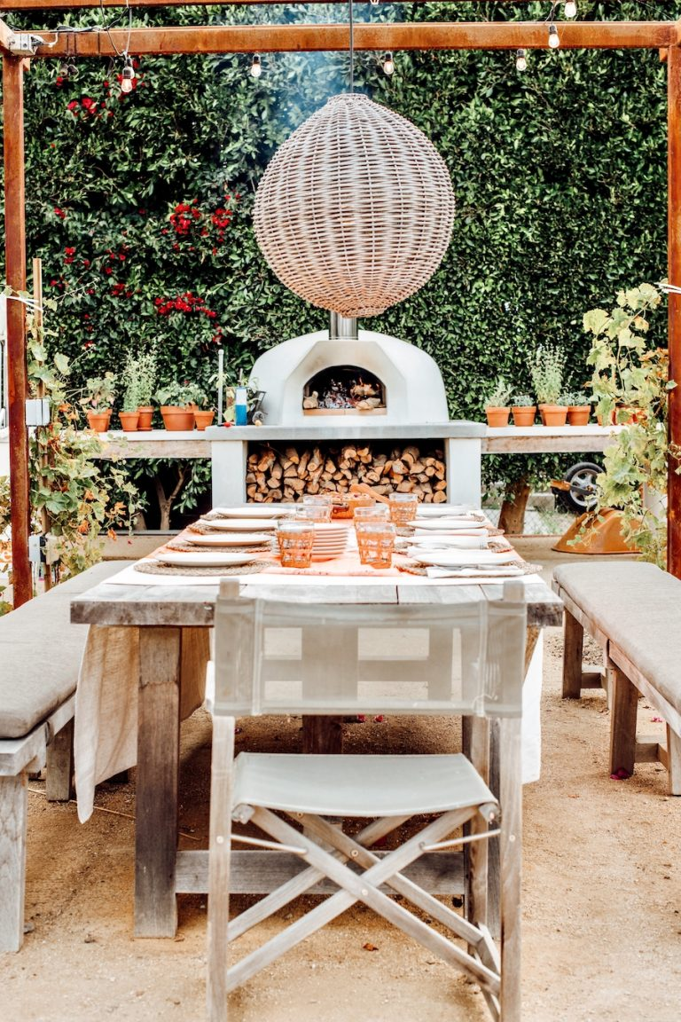 Covered outdoor dining table pergola with woven light fixture pendant, pizza oven, dinner party at malibu farm